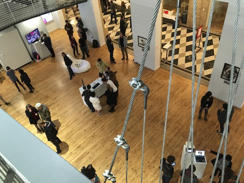 A photo taken from overhead showing groups of people clustered around various artworks displayed on small white tables.